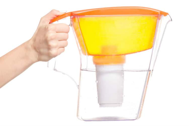 A person is holding a water pitcher filter