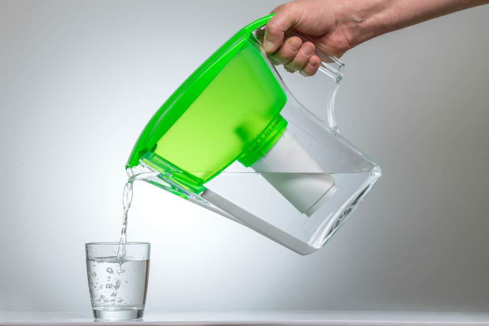 pouring water in the glass from water filter pitcher