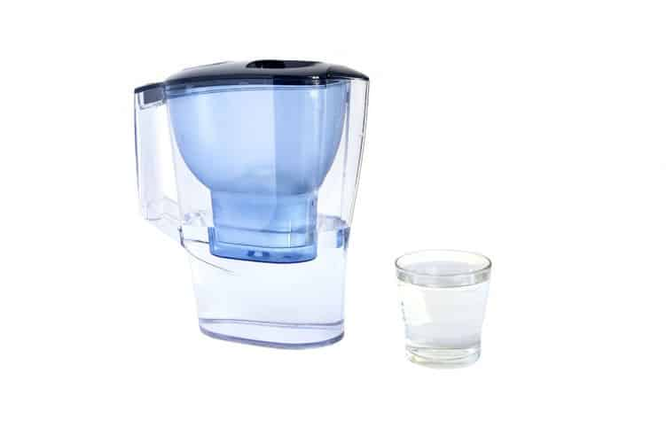 a glass and a water filter pitcher