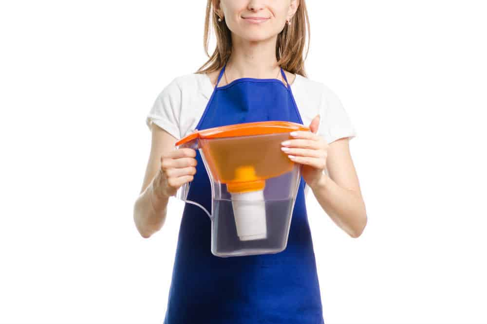 A woman is holding a filtered pitcher