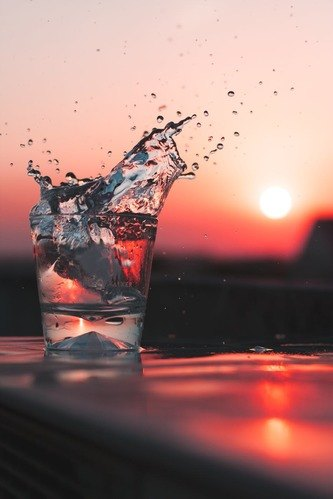 a glass of water and the red sun